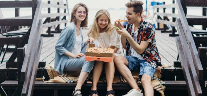 Three friends sharing a pizza and laughter.