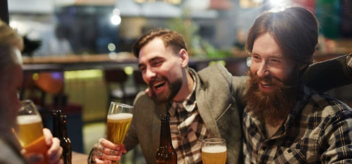 Male friends laughing while drinking beers.