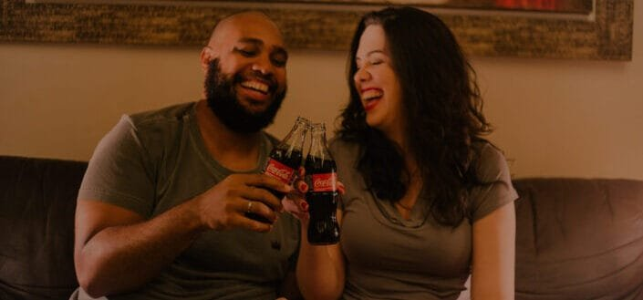 couple toasting a bottle of coca-cola