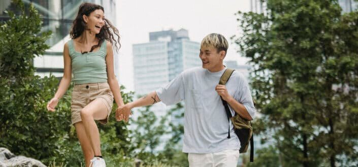 asian couple laughing and holding hands