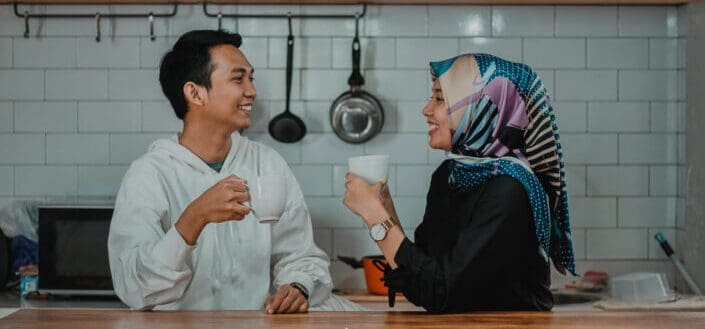 muslim couple smiling at each other with a cup on their hands