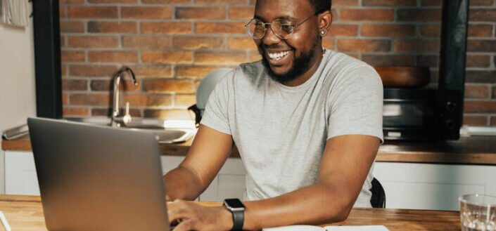 guy smiling in front of laptop