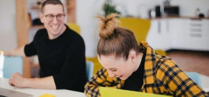 man and woman laughing inside their office