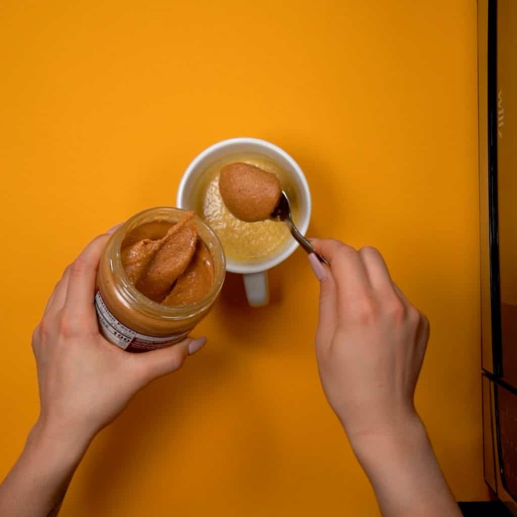 peanut butter being adding to a white batter in a coffee mug