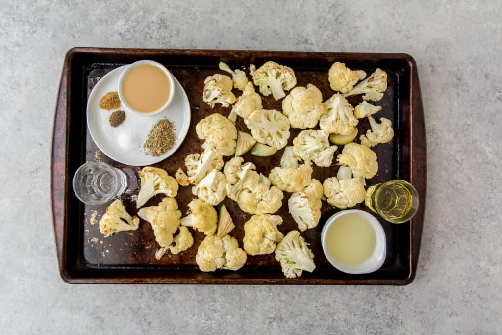roasted cauliflower and garlic on a baking sheet with olive oil, tahini and seasonings