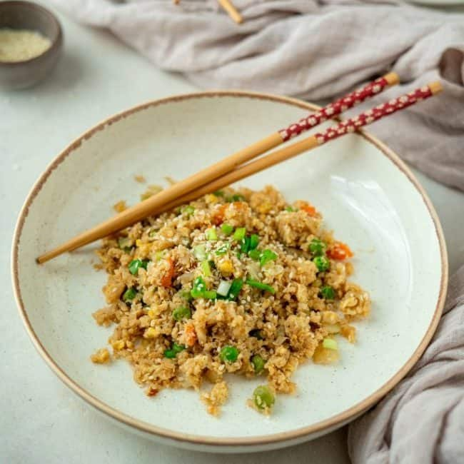 serving of cauliflower fried rice with chopsticks in a bowl