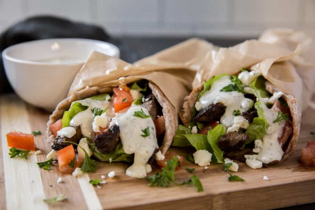 two gyros with yogurt sauce for dipping.