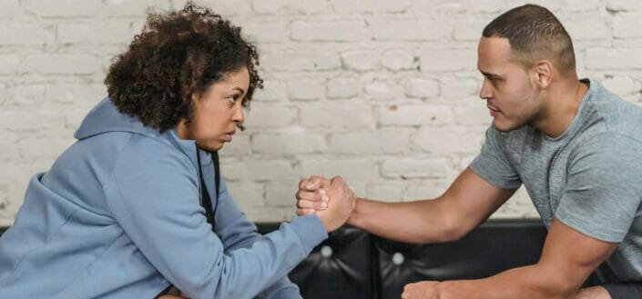 strong couple clasping hands in gym