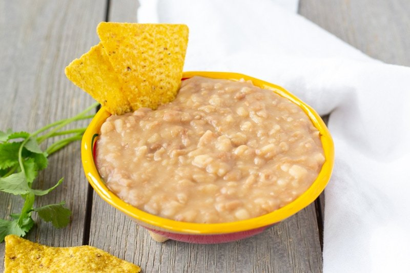 Refried Peruvian beans in a small yellow bowl with tortilla chips on the side.
