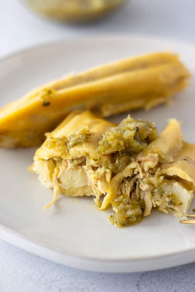 Two tamales on a plate with one cut in half to see filling.