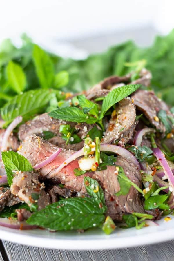 Close up of Sliced beef, onions, mint, and cilantro.