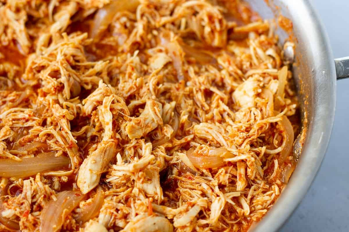 Cooked shredded chicken, onions, and red sauce in a skillet.