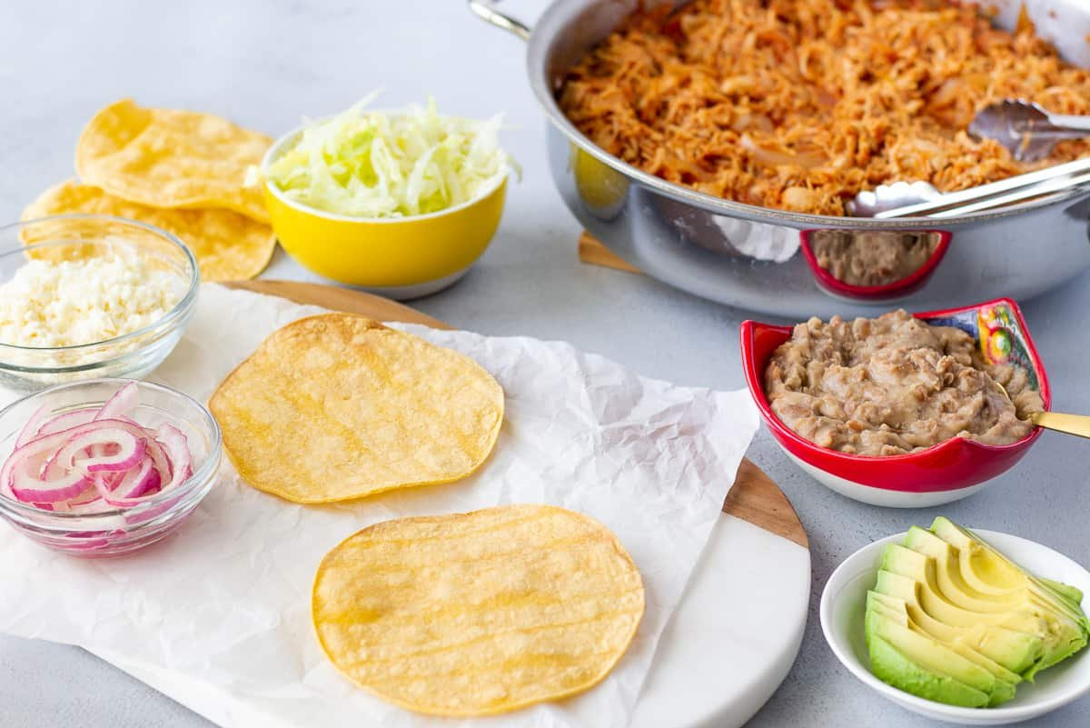 Ingredients in separate bowls with tostadas on a board.
