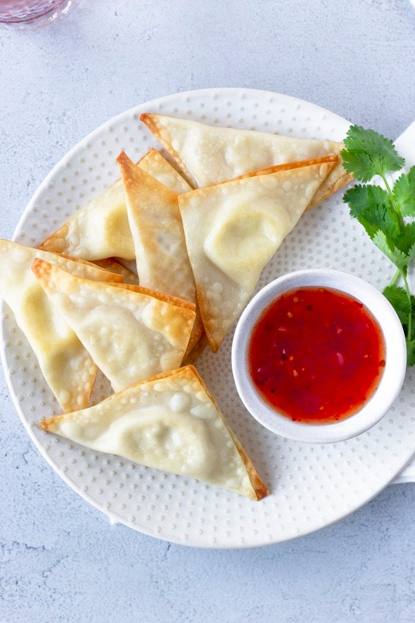 Overhead view of triangle wontons on a plate with a side of sweet chili sauce and garnish of cilantro.