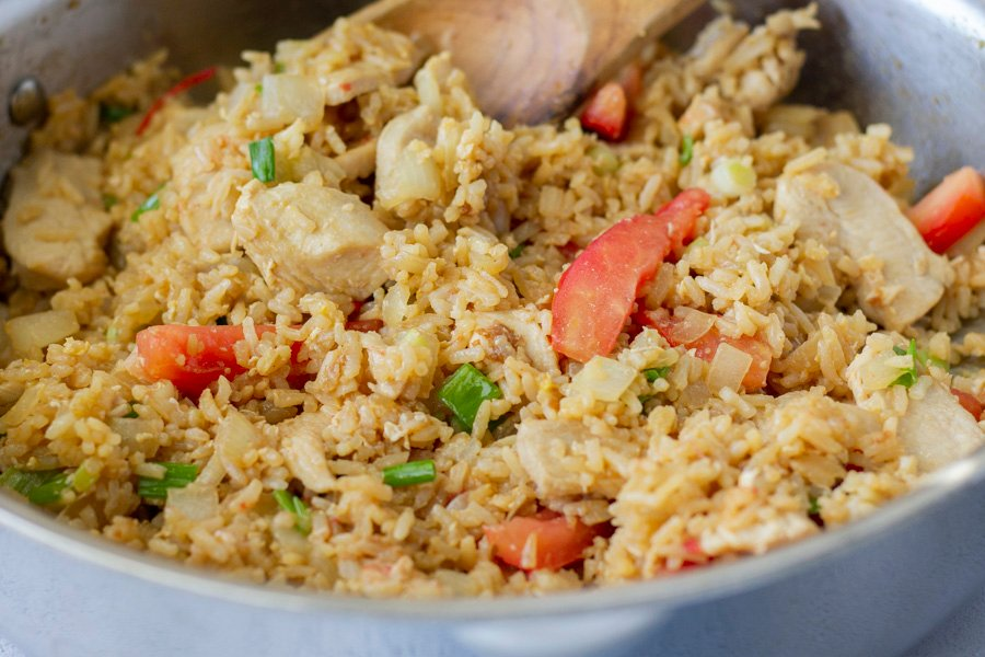 Fried Rice in a stainless steal skillet and a wooden spatula.