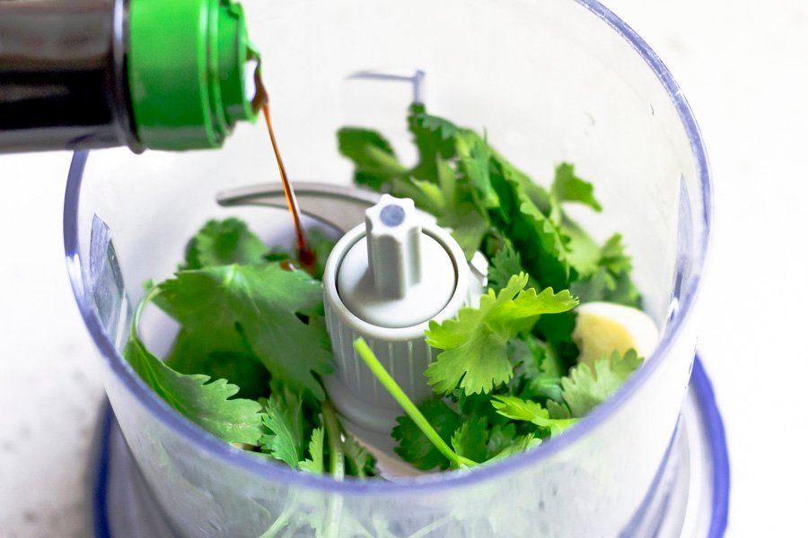 Soy sauce being added into cilantro and garlic mixture.