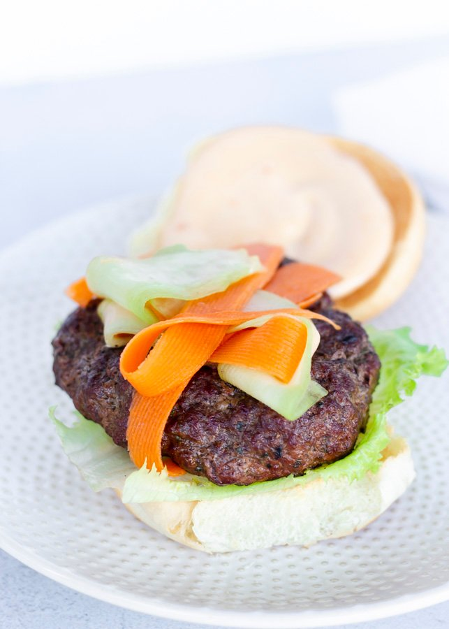 Overhead view of Thai burger with top bun on the side.