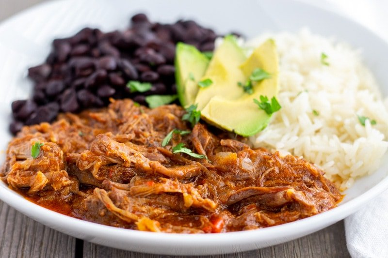 White bowl with pot roast on one half, white rice and black beans on the other half. Topped with Avocado slices.