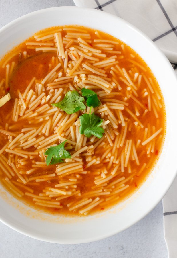 Overhead view of fideo in a white bowl topped with cilantro.