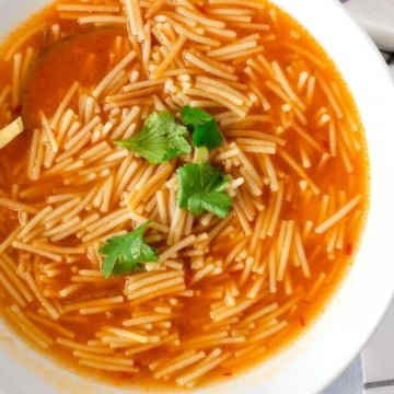 Noodles in a tomato based broth and garnished with cilantro.