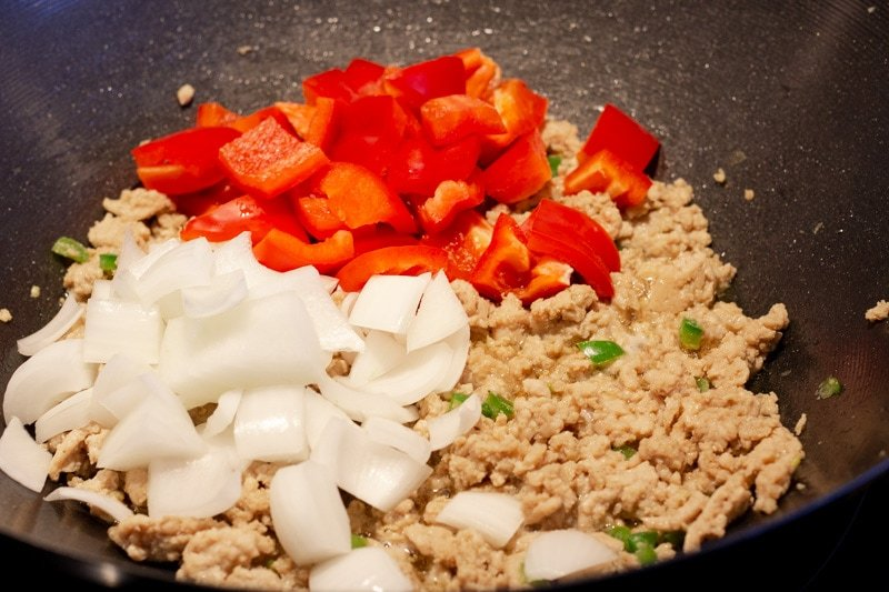 Adding onions and bell pepper to wok.