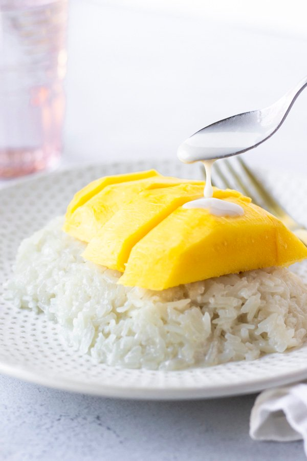 Spoon with coconut milk pouring over mango pieces.
