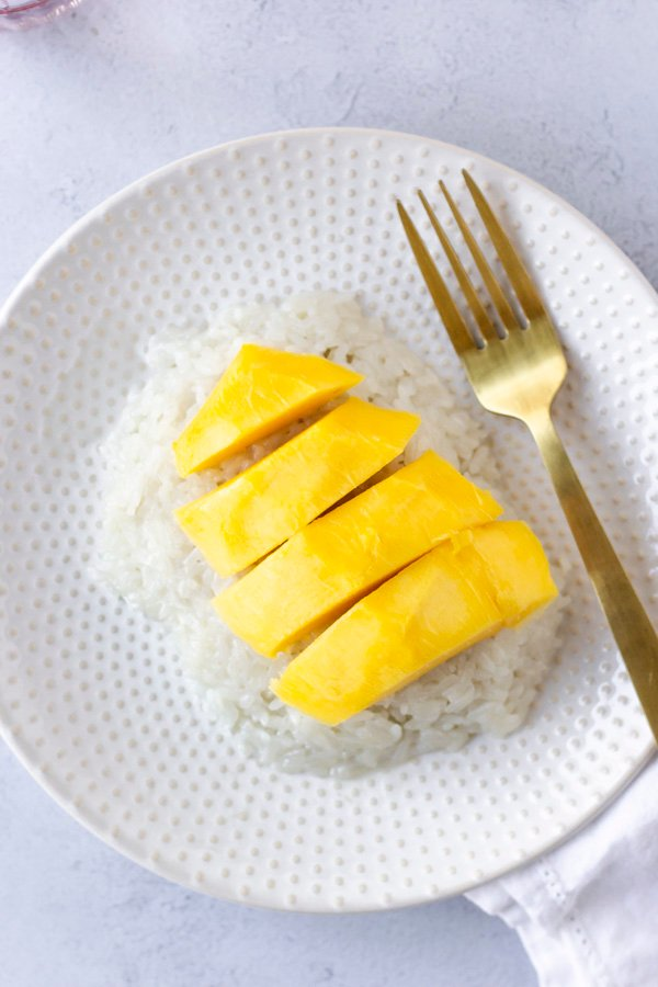 Overhead view of sticky rice with mango on a plate.