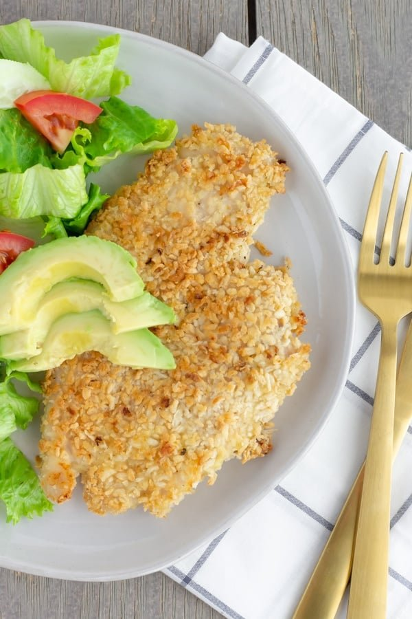 Chicken milanesa on a white plate with a side salad.