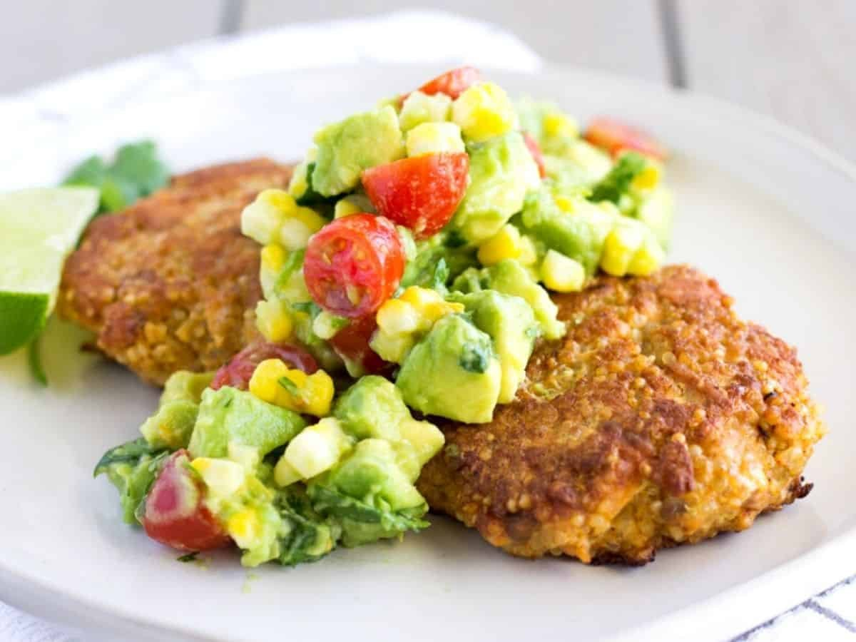 Horizontal view of 2 salmon cakes on a white plate with avocado corn salsa on top.