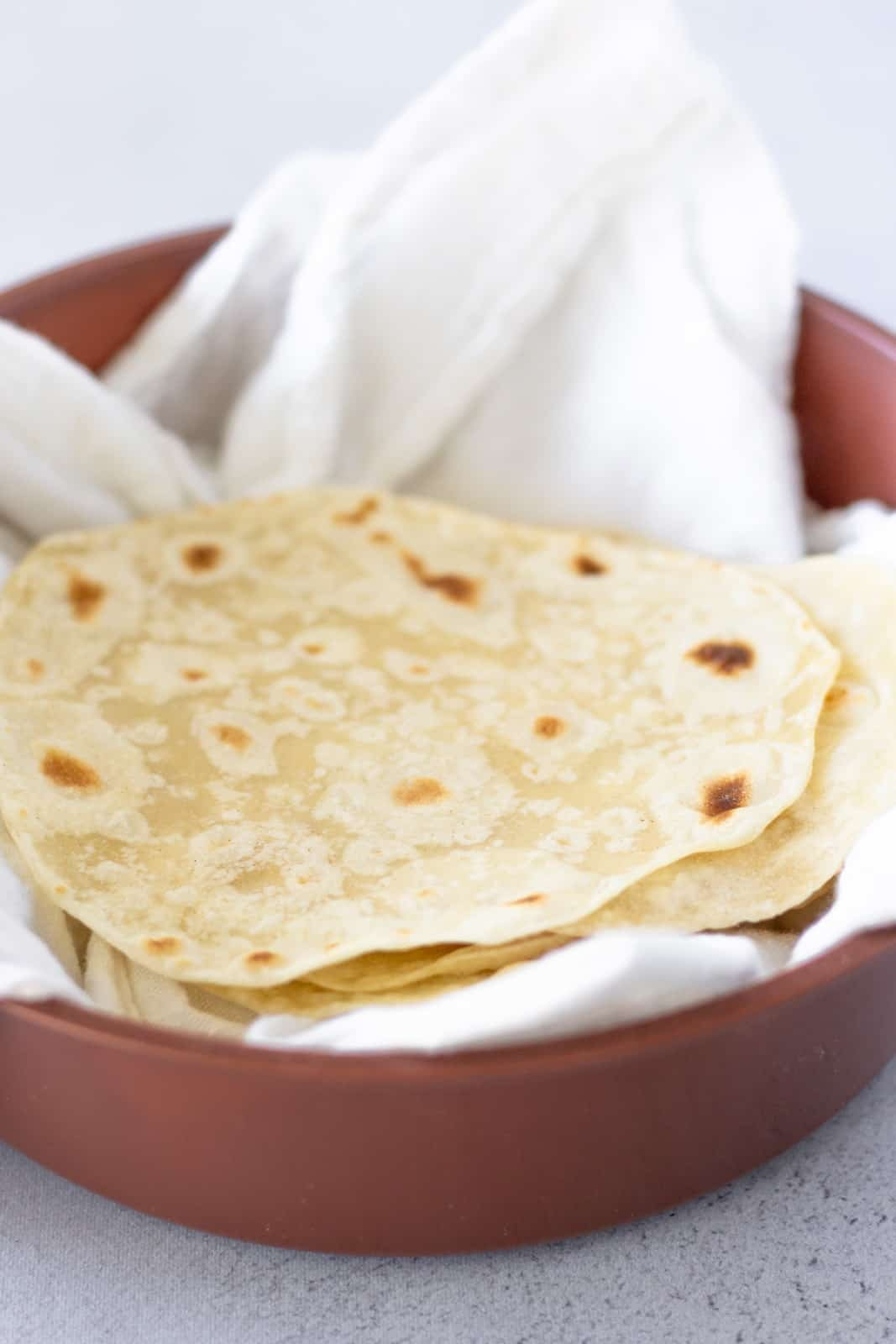Tortillas stacked in a brown tortilla warmer with a white cloth inside.