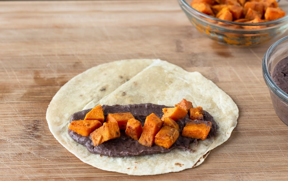 Flour Tortilla on a cutting board layered with black beans and sweet potato.