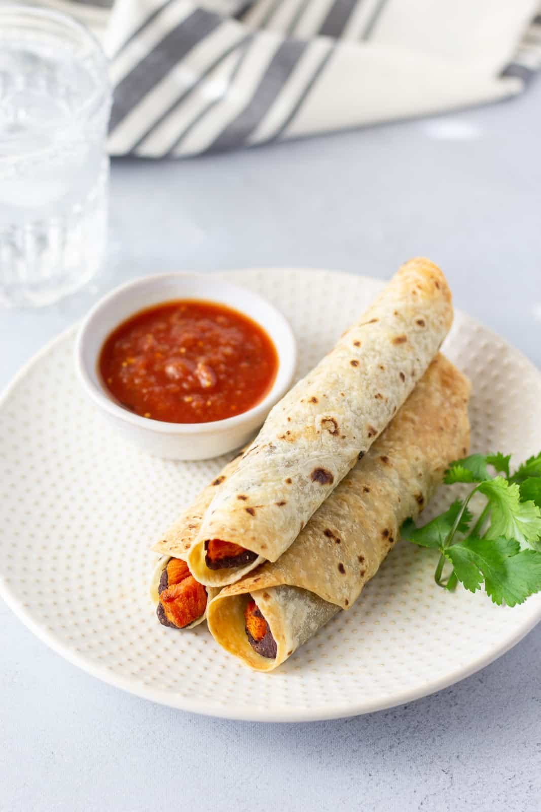 3 sweet potato flautas on a plate with a side of salsa and cilantro garnish.