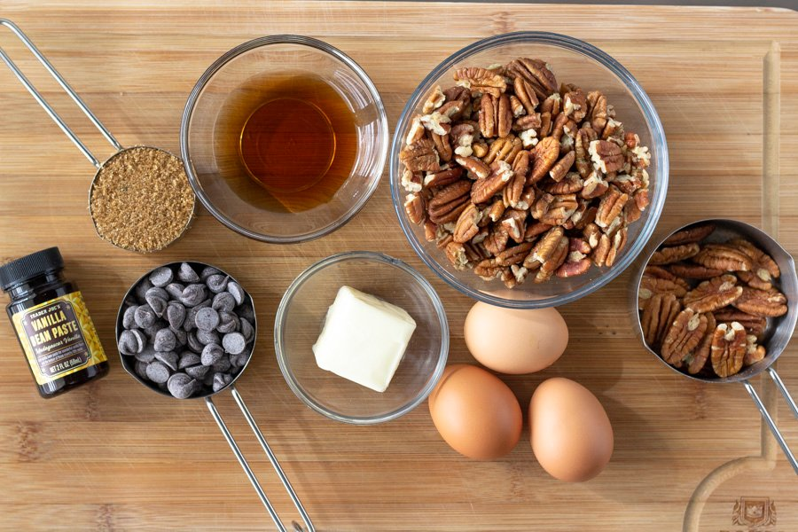 Overhead view of ingredients on a cutting board. Pecans, eggs, butter, agave, chocolate chips, brown sugar, and vanilla.