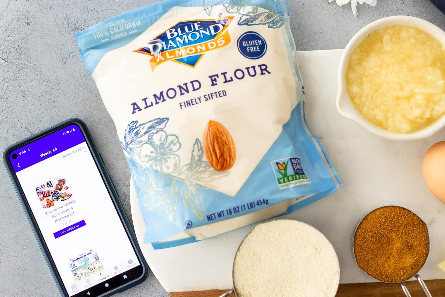 Cell phone with the Albertson's app and Almond Flour package with other ingredients.