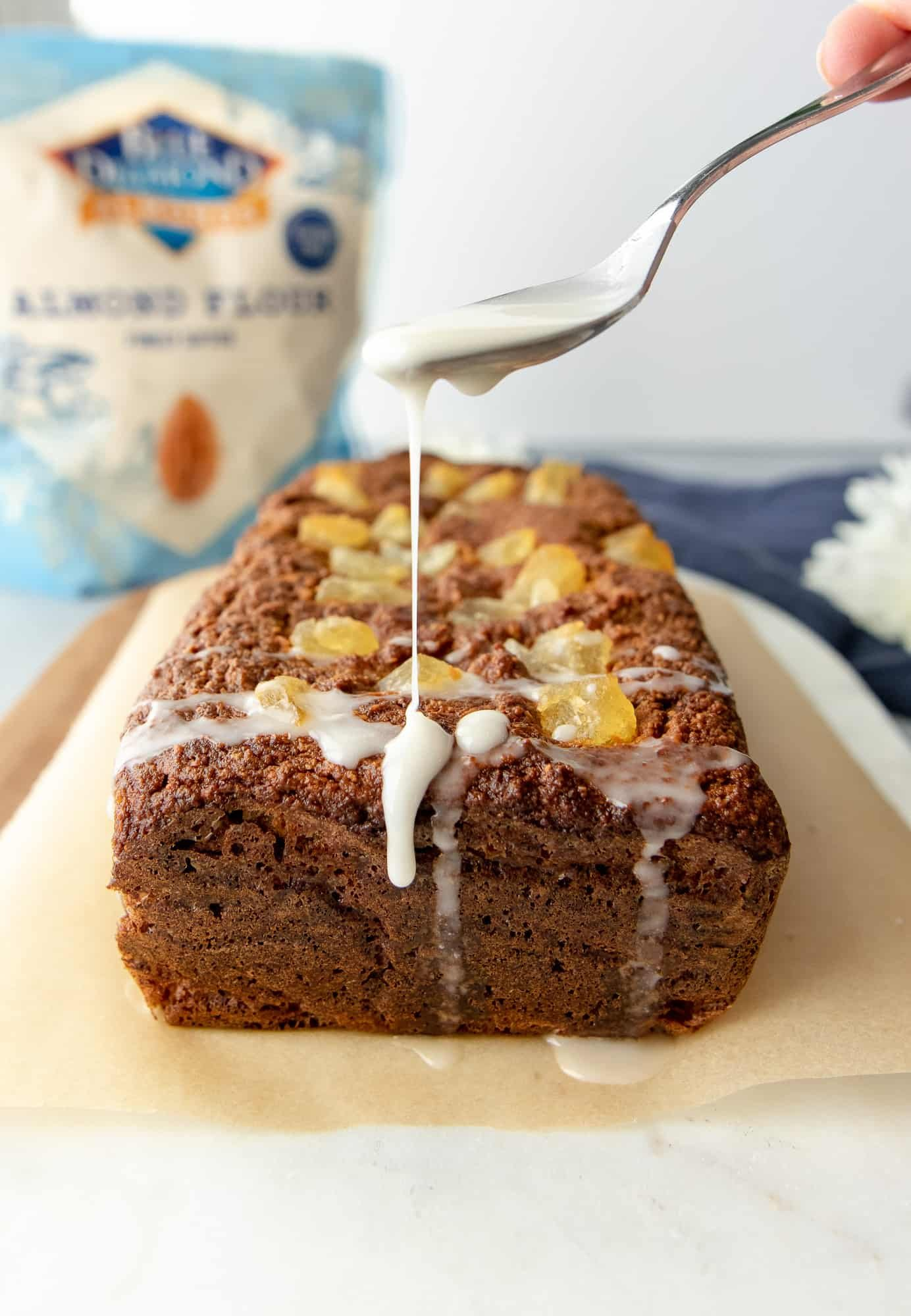 Pineapple loaf whole with spoon drizzling coconut cream on top.