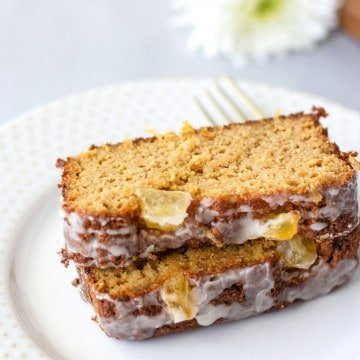 2 slices of pineapple loaf cake on a plate with a fork on the side.