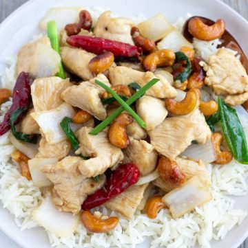 Thai Cashew Chicken Stir fry with roasted chili peppers, onions, juicy chicken, and crunchy cashews- ThaiCaliente.com