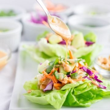 Spoon drizzling peanut sauce over lettuce wrap.