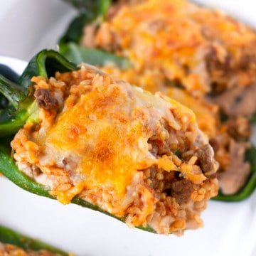 Stuffed Poblano being lifted from the pan of other poblanos.