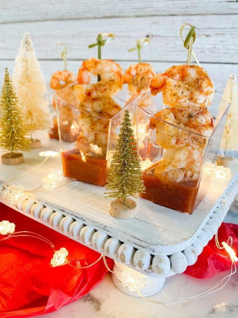 Clear cups filled with cocktail sauce and 3 shrimp on a skewer inside. Decorative mini Christmas are around the tray.