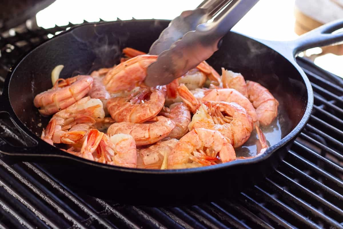Shrimp cooking on the grill in a cast iron skillet.