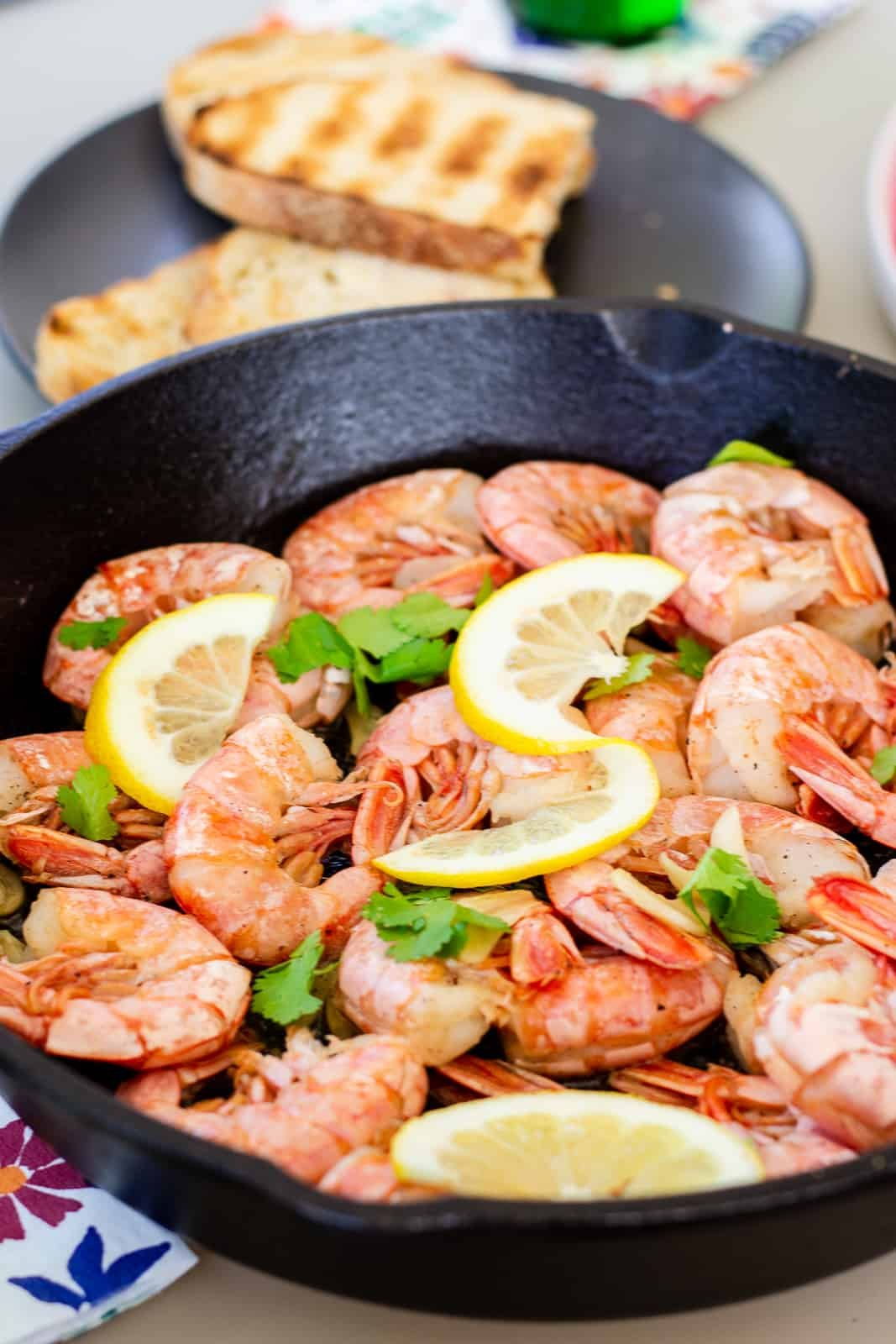 Shrimp in a cast iron skillet garnished with lemon slices and cilantro leaves.