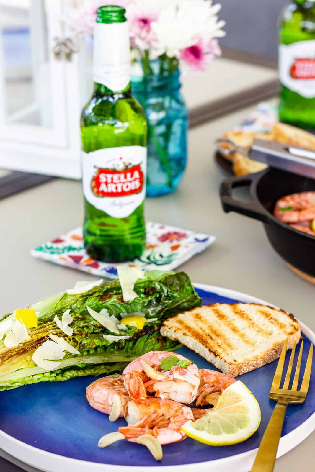 Blue plate with shrimp, slice of grilled bread, halved grilled romaine, and a bottle of Stella Artois Beer.