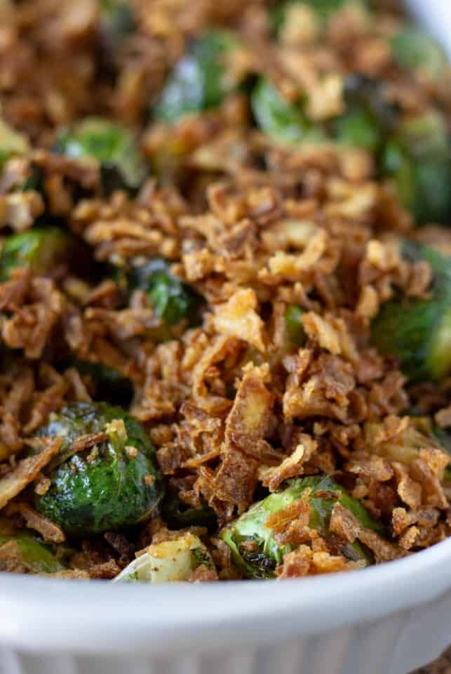 Up close view of roasted brussel sprouts in a white serving dish