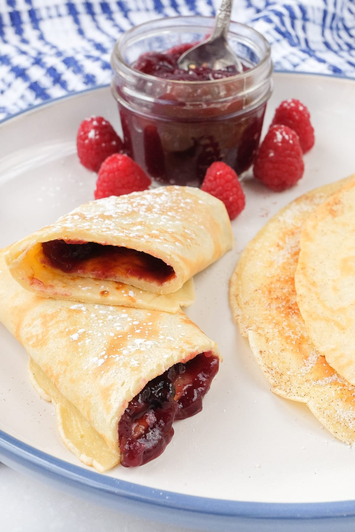 german pancake rolled with jam with berries and jam behind on plate