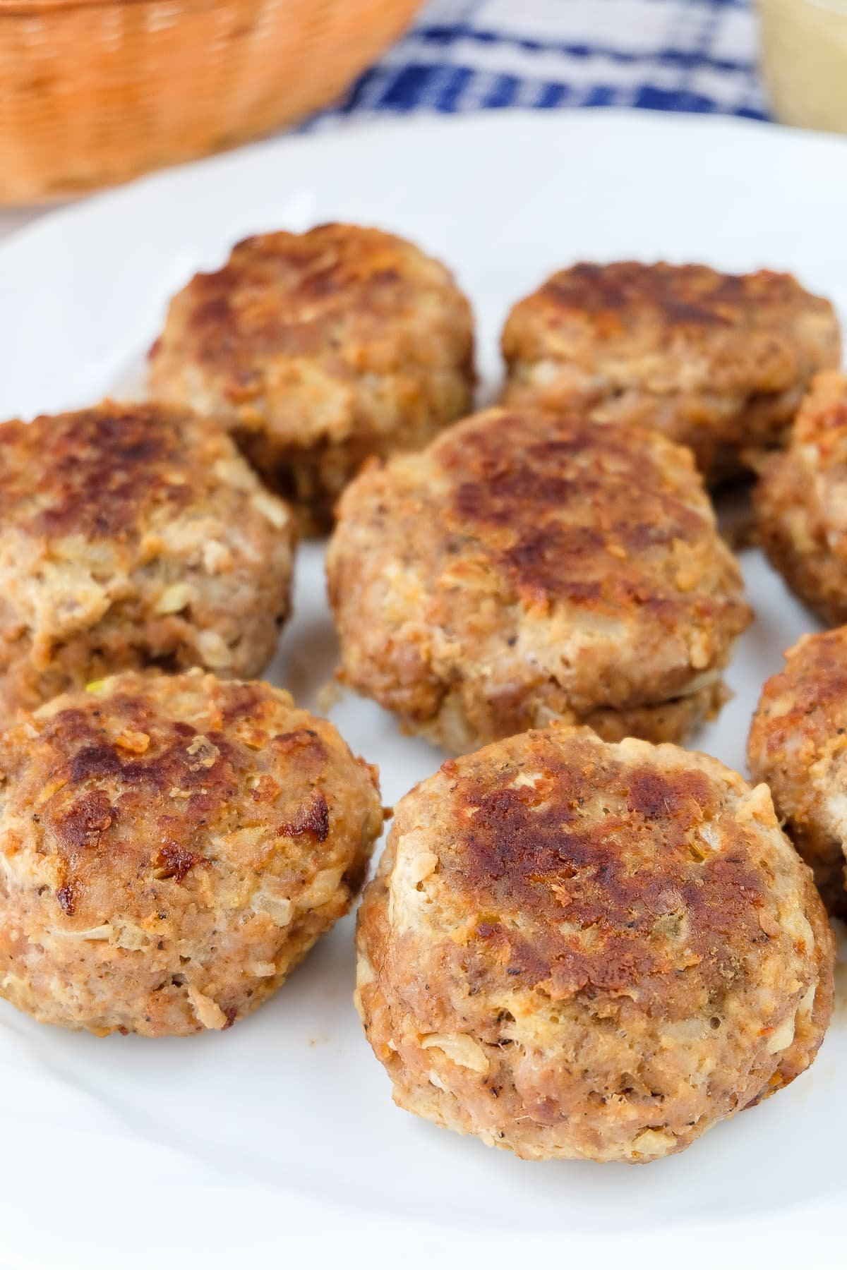 fried german meatballs arranged on white plate with mustard behind