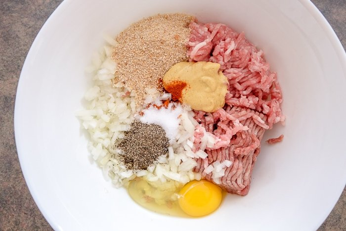ingredients for german meatballs in white mixing bowl on counter
