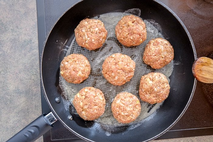 raw meatballs frying in butter in frying pan on stove