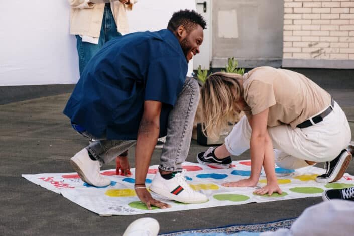 Man and woman playing outdoor twister