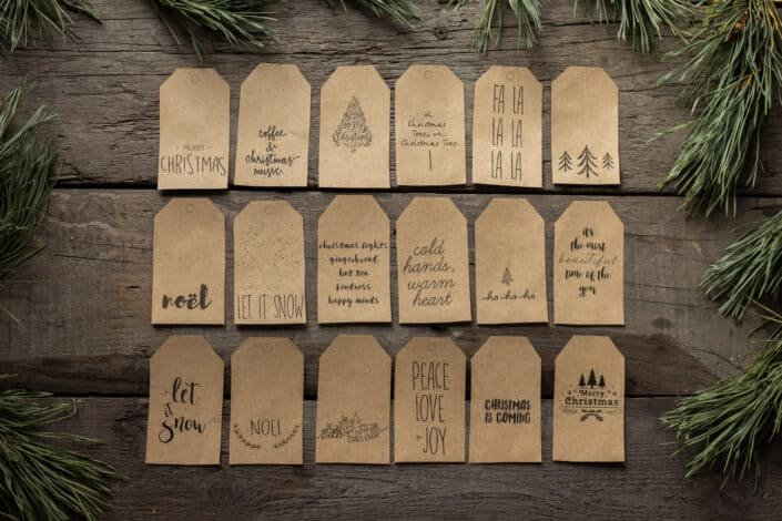 Collection of christmas tags placed on wooden surface